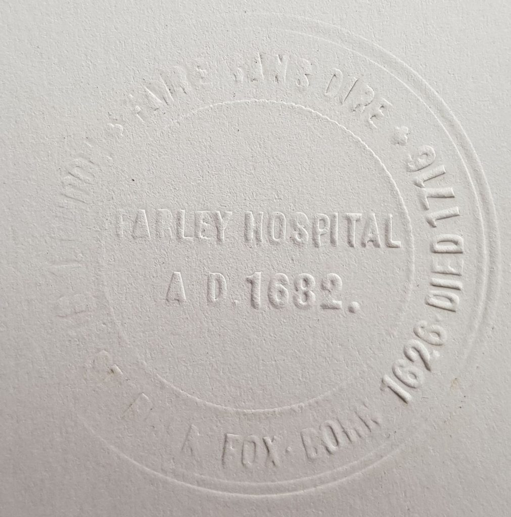 """paper that has been stamped, some text not readable as the stamp is old, but which says """"Farley Hospital A.D. 1682. Sir Stephen Fox. Born 1626. Died 1716."""" There is also some Latin which is not readable."""